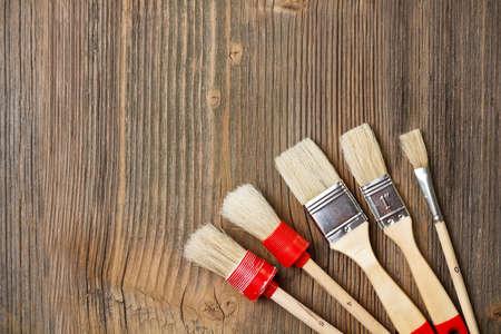 Paint brushes on vintage wooden background photo