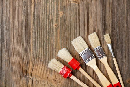 craft work: Paint brushes on vintage wooden background