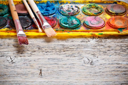 paintbox: Closeup of messy, used watercolor paintbox on wood background
