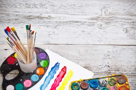 craft materials: Box of watercolors and paintbrushes on wooden desk