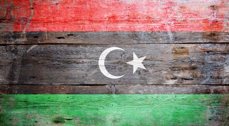 Flag of Libya painted on grungy wood plank background  photo