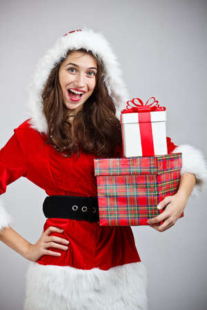 Christmas woman holding gifts wearing Santa Claus costume photo
