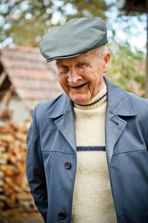Outdoor portrait of smiling senior man in hat