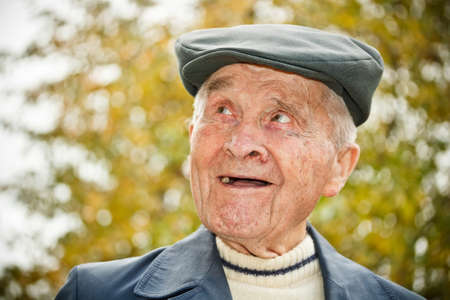 old man smiling: Outdoor portrait of smiling elderly man in hat  Stock Photo