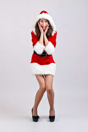 Christmas girl with red santa dress shocked and surprised photo