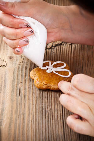 Womans hand which is decorating Christmas gingerbread photo