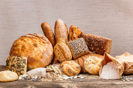 Different kinds of fresh bread on wooden table  photo