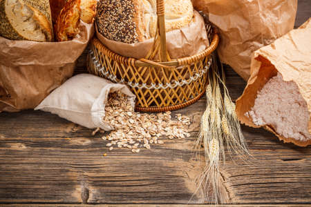 Composition with bread and rolls in wicker basket and paper bag  photo