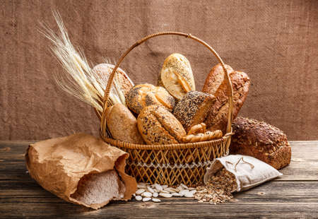 Fresh bread in the basket on wooden background  photo