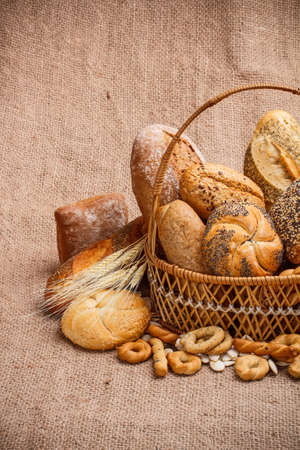 Various breads in basket on burlap tablecloth photo