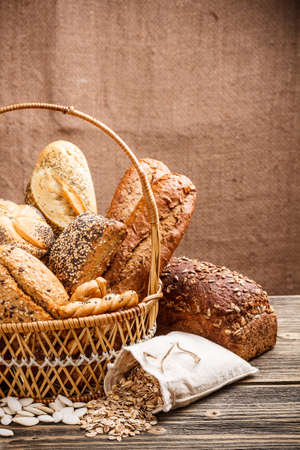 Basket of bread on old wooden table Stock Photo - 17461942