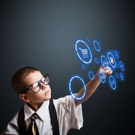 Boy in an adult business suit choosing shopping cart button Stock Photo - 17450351