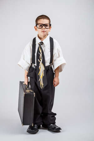 Serious little business boy holding office briefcase Stock Photo
