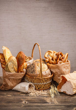 Composition with bread and rolls in wicker basket and paper bag Stock Photo - 17513743