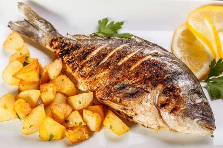 daurade: Dorade poisson avec pommes de terre sur une plaque blanche gros plan