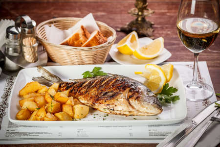 Grilled dorada garnished with potato and lemon photo