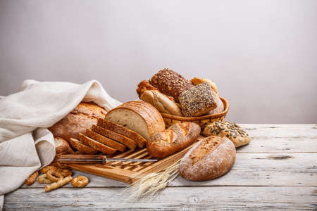 Mix of bread on cutting board and on basket Stock Photo