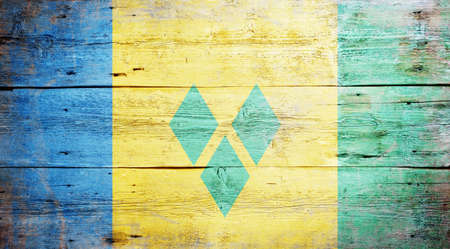 Flag of Saint Vincent and the Grenadines painted on grungy wood plank background Stock Photo - 17653025