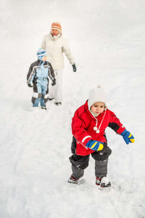 to go sledding: Winter time, little boy going up on a hill, mother and brother on background Stock Photo