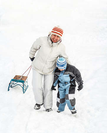 to go sledding: Mother and son going up on a hill pulling a sledge