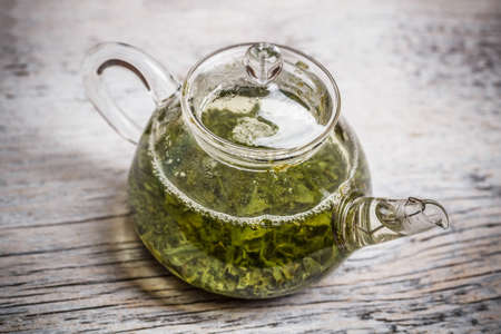 Green tea in glass teapot on vintage wooden table photo