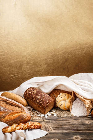 Mix of bread on old wooden tabel with golden background