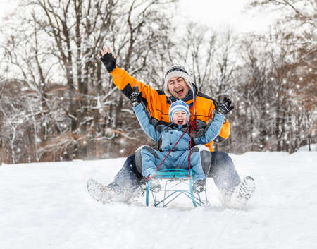 cold weather: Father and son sledding at winter time