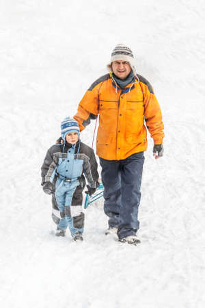 to go sledding: Father and son going up on a hill pulling a sledge Stock Photo