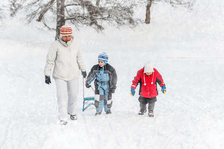 to go sledding: Mother and sons going up on a hill pulling a sledge Stock Photo