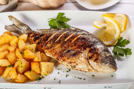bass fish: Whole fried dorado served with lemons and potato
