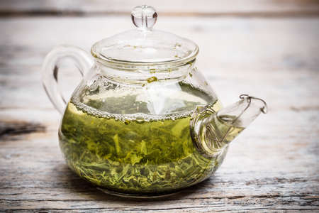 Glass teapot with green tea on wooden table photo