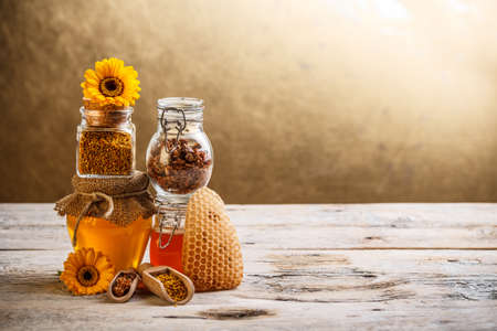 Decorative display with jars of fresh honey, flower pollen and propolis photo