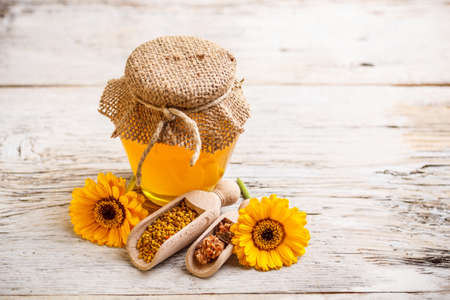 Still life of jars of honey,pollen and propolis with a spoon Stock Photo - 17653054