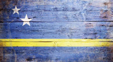 Flag of Curacao painted on grungy wood plank background