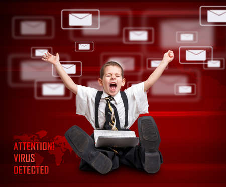 Little boy in business suit screaming and looking worried while using a computer.  photo