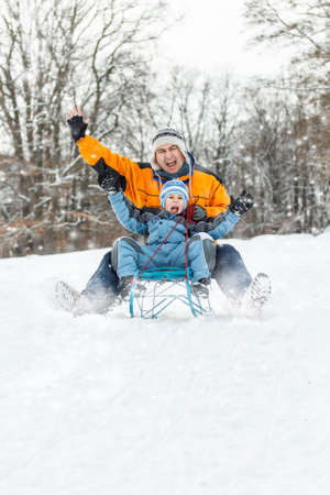 Father and son sledging, nice winter scene  photo