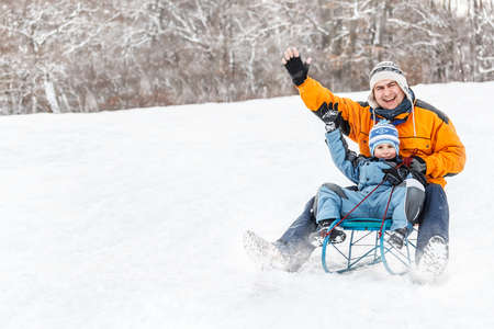 Young father and son sledding at winter time photo