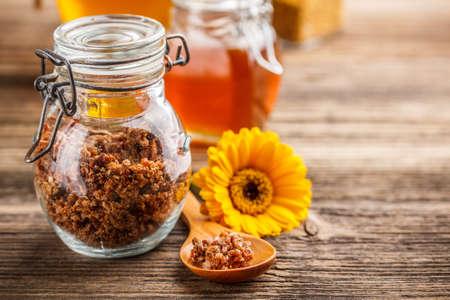 Propolis granule in glass jar with spoon and flower
