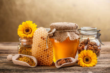 bee on flower: Still life with honey, honeycomb, pollen and propolis Stock Photo