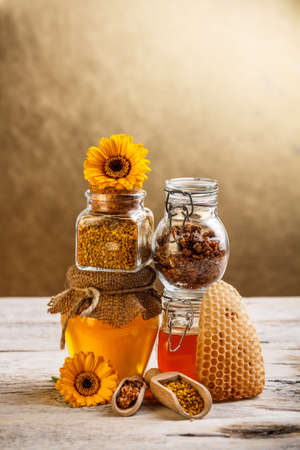 Honeycomb and glass jar of honey, pollen, propolis photo