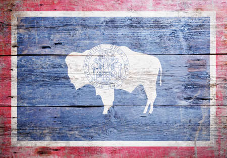 Flag of the state of Wyoming  painted on grungy wooden background Stock Photo - 17787749