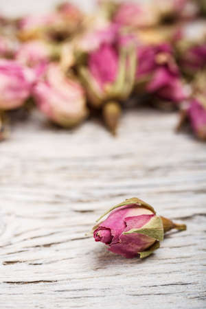 Dried rose buds on wooden table photo