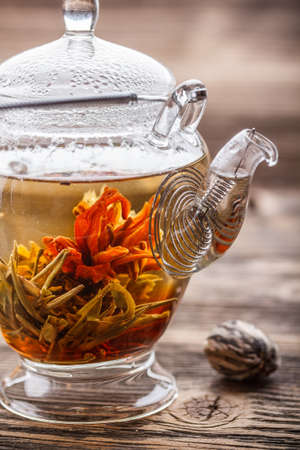 unfurl: Blooming tea in glass teapot on rustic wooden table Stock Photo