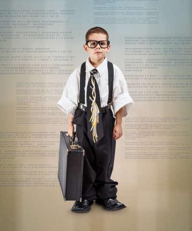 Volledige lengte shot van ernstige kleine zakelijke jongen
