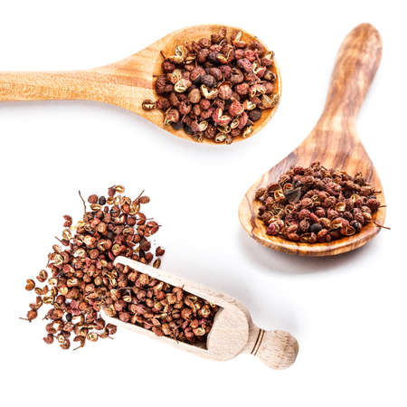 Wooden shovels with sichuan pepper on white background Stock Photo