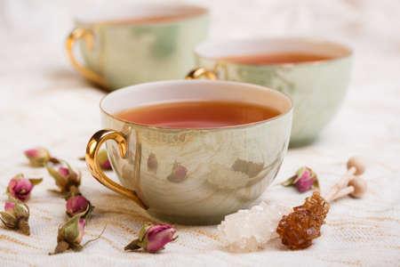 tazza di te: Tazza di tè con bocciolo di rosa e di roccia bastoncini di zucchero