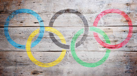 Olympic flag painted on grungy wood plank background