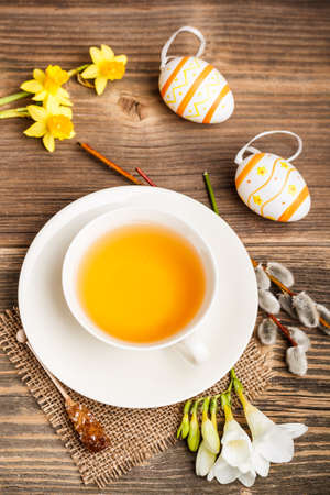 Easter composition of tea cup, eggs and flowers  photo
