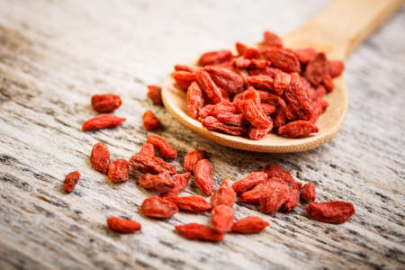 Wooden tablespoon of dried goji berries photo