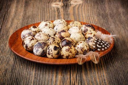 huevos de codorniz: Huevos de codorniz en un plato de madera